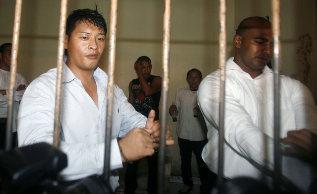 Australians Andrew Chan (L) and Myuran Sukumaran wait in a temporary cell for their appeal hearing in Denpasar District Court in Indonesia's resort island of Bali in this September 21, 2010 file photo. The two convicted drug smugglers were transferred on March 4, 2015, from a Bali prison to an island for execution along with other foreigners, underlining Indonesia's determination to use the death penalty despite international criticism. REUTERS/Murdani Usman/Files