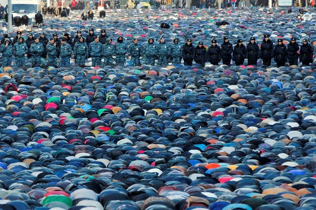 Russian police officers stand guard as Muslims pray outside the main Moscow mosque during celebrations of Eid al-Adha, a feast celebrated by Muslims worldwide, which Muslims in Russia call Kurban-Bairam in Moscow, Russia, Tuesday, October 15, 2013. According to the press service of Moscow's main police department, about four thousand police officers, Interior troops and others will be ensuring security during the Eid al-Adha celebration events. (Photo by Evgeny Feldman/AP Photo)