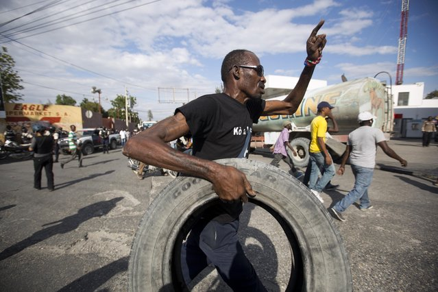 A protester carries a tire to burn during a street protest after it was announced that the runoff Jan. 24, presidential election had been postponed, in Port-au-Prince, Haiti, Friday, January 22, 2016. (Photo by Dieu Nalio Chery/AP Photo)