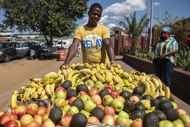 Fruit vendor Paul Machaieie pushes his fruit cart as he looks for clients along the pavement outside the Lenasia Magistrates Court, Johannesburg on March 19, 2021. (Photo by Michel Bega)