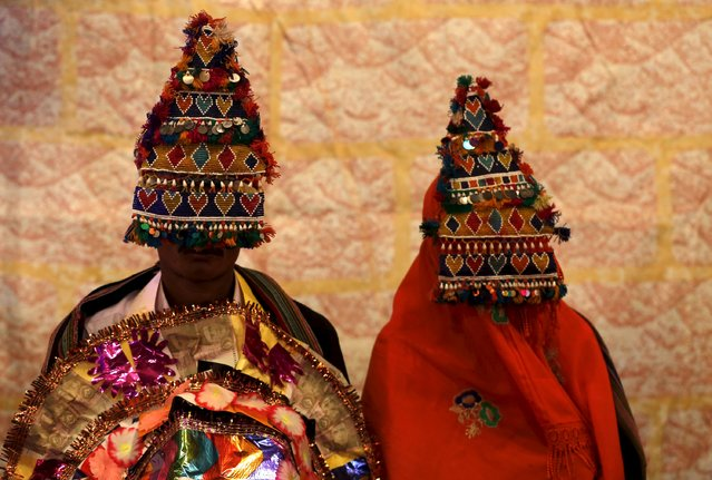 A bride and groom wearing traditional handmade garlands wait for their wedding to start during a mass marriage ceremony in Karachi, Pakistan, January 24, 2016. (Photo by Akhtar Soomro/Reuters)