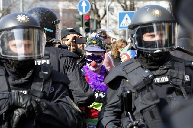 An anti-capitalist protester dressed as a clown stands behind policemen near the European Central Bank (ECB) building before the official opening of its new headquarters in Frankfurt March 18, 2015. (Photo by Michael Dalder/Reuters)