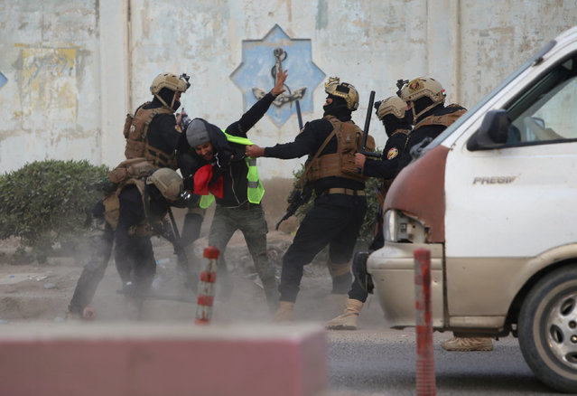 Iraqi security forces detain a demonstrator during an anti-government protest near the government building in Basra, Iraq on December 4, 2018. (Photo by Essam al-Sudani/Reuters)