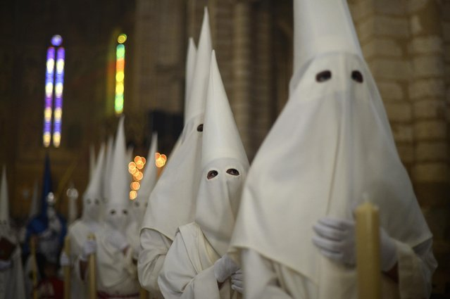 """Hooded penitents from """"La Borriquita"""" brotherhood take part during a Holy Week procession in Cordoba, Spain, Sunday, March 29, 2015. (Photo by Manu Fernandez/AP Photo)"""