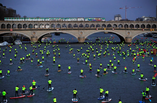 Participants make their way in the 9th Edition of the Nautic SUP Paris Crossing stand up paddle competition on the river Seine in Paris, France, December 9, 2018. (Photo by Gonzalo Fuentes/Reuters)