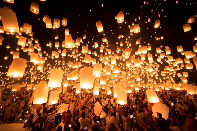 In this photo taken Saturday, November 16, 2013,  thousands of paper-made balloons, powered by burning oil, rise into the evening sky in Chiang Mai province, some 580 kilometers (360 miles) north of Bangkok during the Loy Krathong Festival. During the festival at night time,  Thais float lanterns to the sky and float candles on the lotus-shaped basket into the rivers, in order to drift away their bad luck. (Photo by Vincent Thian/AP Photo)
