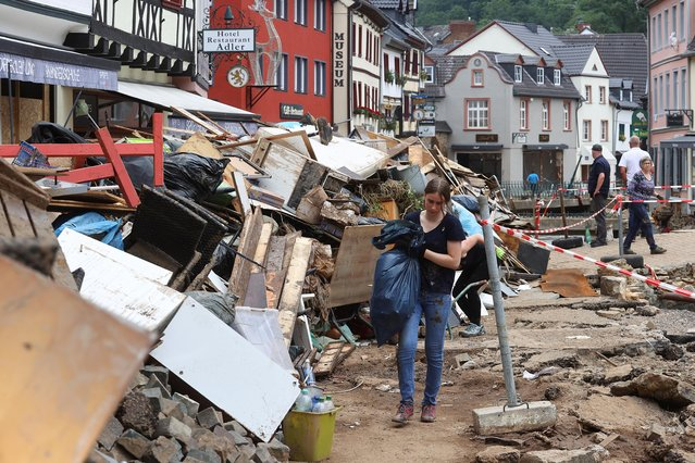 A woman carries a bag in an area affected by floods caused by heavy rainfalls in Bad Muenstereifel, Germany, July 19, 2021. (Photo by Wolfgang Rattay/Reuters)