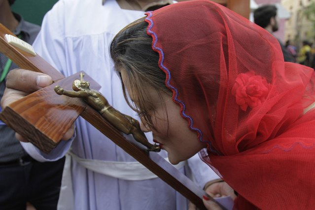 A Pakistani Christian woman kisses a representation of the Christ during a Mass on Good Friday in a church in Lahore, Pakistan, Friday, April 3, 2015. Christians around the world are marking the Easter holy week. (Photo by K. M. Chaudary/AP Photo)