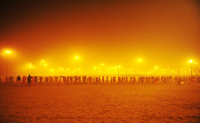 Sadhus or holy men walk in a procession towards the Sangham or the confluence of the the Yamuna and Ganges rivers to bathe before sunrise during the Kumbh Mela in Allahabad on January 14, 2013. (Photo by Sanjay Kanojia/AFP Photo)