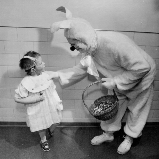 March 24, 1989 Back in action, delivering cheer 61-year-old Elmer Buller, returned to the burn unit at St. Paul-Ramsey Medical Center Thursday, but his time as an Easter Rabbit. He offered words of encouragement and some candy to Justina Drozda, 3. (Photo by Regene Radniecki/Minneapolis Star Tribune)