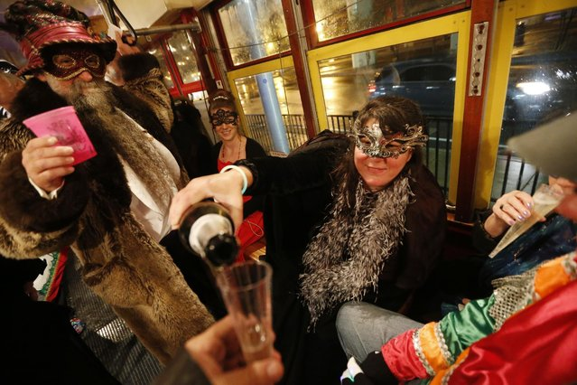 """Members of the """"Societe des Champs Elysee"""" riding the Rampart-St. Claude street car line, which just opened last fall, pour champagne to commemorate the official start of Mardi Gras season, in New Orleans, Friday, January 6, 2017. (Photo by Gerald Herbert/AP Photo)"""