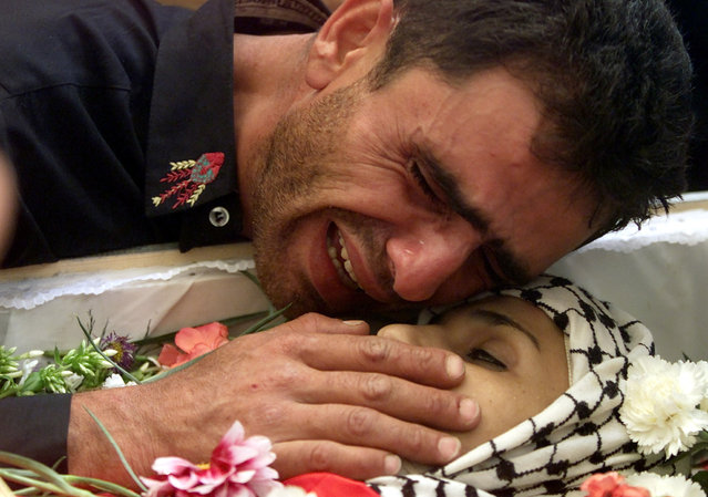 A Palestinian Christian cries over the body of his wife killed in the crossfire between Palestinians and Israeli troops in the West bank town of Bethlehem, October 2001. (Photo by Desmond Boylan/Reuters)