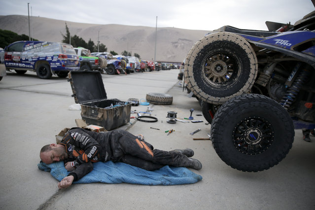 Co-driver Bill Conger, of United States, rests next to his Tetron prior to the stage five of the Dakar Rally between Tacna and Arequipa, Peru, Friday, January 11, 2019. (Photo by Ricardo Mazalan/AP Photo)