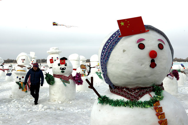 A man walks between snowmen on Songhua River that displays 2019 snowmen as a part of annual ice festival, in the northern city of Harbin, Heilongjiang province, China January 4, 2019. (Photo by Tyrone Siu/Reuters)