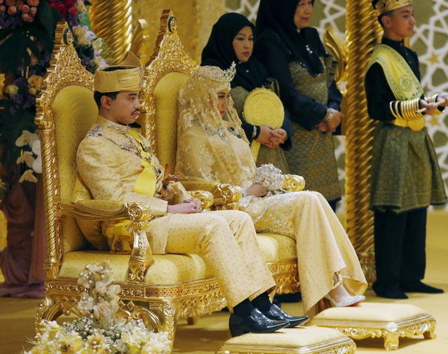 "Brunei's newly wed royal couple, Prince Abdul Malik and Dayangku Raabi'atul 'Adawiyyah Pengiran Haji Bolkiah, sit during the ""bersanding"" or enthronement ceremony at their wedding in the Nurul Iman Palace in Bandar Seri Begawan April 12, 2015. (Photo by Olivia Harris/Reuters)"