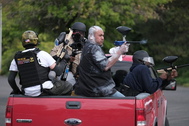 """Tusitala """"Tiny"""" Toese, a member of the far-right group Proud Boys, fires paintball rounds at anti-fascist protesters as they depart from their rally on Sunday, August 22, 2021, in Portland, Ore. (Photo by Alex Milan Tracy/AP Photo)"""
