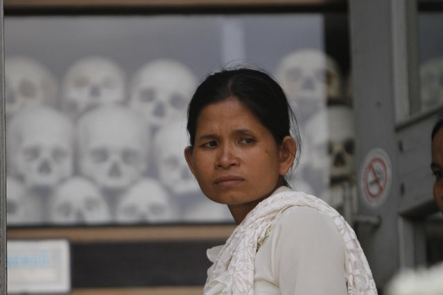 A woman stands in front of the stupa containing hundreds of human skulls and bones of victims in Khmer Rouge regime, at Choeung Ek memorial on the outskirts of Phnom Penh, Cambodia, Friday, April 17, 2015. (Photo by Heng Sinith/AP Photo)