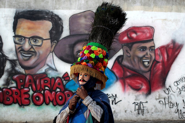 A dancer prepares to participate in the celebration of the feast honoring Saint Sebastian in front of a mural with images of late Venezuela's President Hugo Chavez and Carlos Fonseca, founder of Sandinista party in Diriamba, Nicaragua January 19,2017. (Photo by Oswaldo Rivas/Reuters)