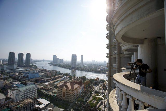 A visitor takes photograghs on a balcony of an abandoned building in Bangkok April 19, 2015. (Photo by Athit Perawongmetha/Reuters)