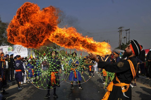 """Sikh devotees show their skill in martial arts during """"Nagar Kirtan"""" carried out as part of """"Prakash Utsav"""", which is the birth anniversary celebrations of Guru Gobind Singh on January 4, 2014 in Jammu, India. Sikhs celebrated the 347th birth anniversary of Guru Gobind Singh, the tenth and last guru of Sikhs. (Photo by Nitin Kanotra/Hindustan Times via Getty Images)"""