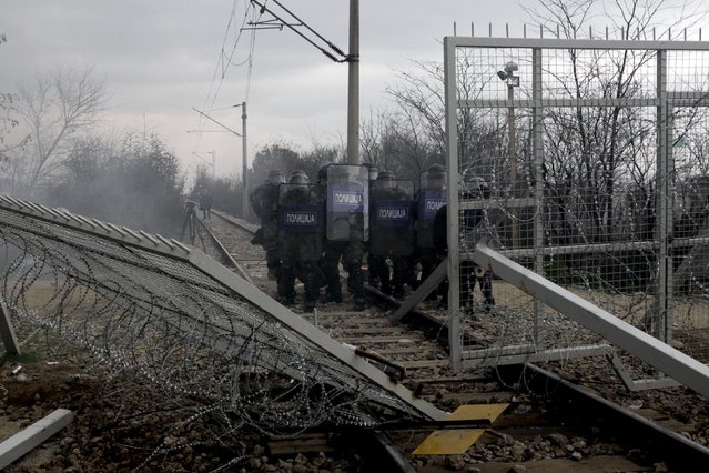 Macedonian riot police officers stand next to part of the border fence brought down by protesting stranded refugees and migrants during a protest at the Greek-Macedonian border, near the Greek village of Idomeni, February 29, 2016. (Photo by Alexandros Avramidis/Reuters)