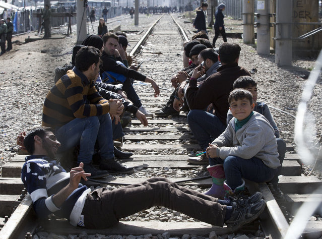 Migrants sit on the rail tracks awaiting on the Greek side of the border to enter Macedonia near the southern Macedonian town of Gevgelija, Tuesday, March 1, 2016. (Photo by Visar Kryeziu/AP Photo)
