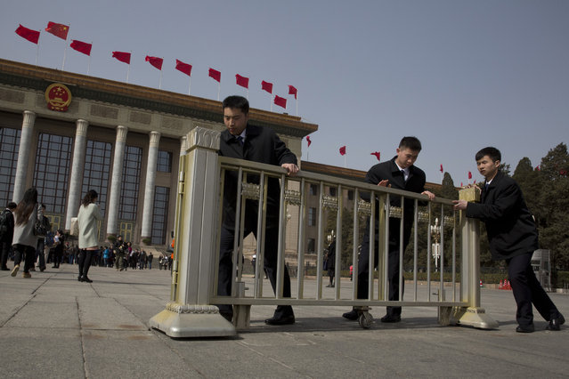 In this Saturday, March 5, 2016 photo, security guards push barriers into place after the opening session of the National People's Congress (NPC) held at the Great Hall of the People in Beijing. (Photo by Ng Han Guan/AP Photo)