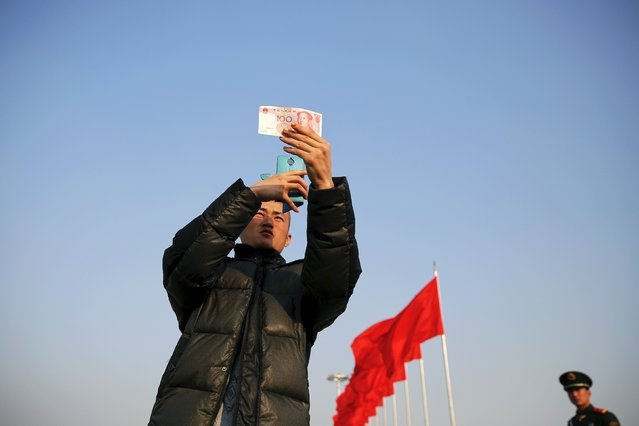 A man takes pictures of a hundred-yuan banknote at the Tiananmen Square as the area near the Great Hall of the People prepares for upcoming annual sessions of the National People's Congress (NPC) and Chinese People's Political Consultative Conference (CPPCC), in Beijing March 2, 2016. (Photo by Damir Sagolj/Reuters)