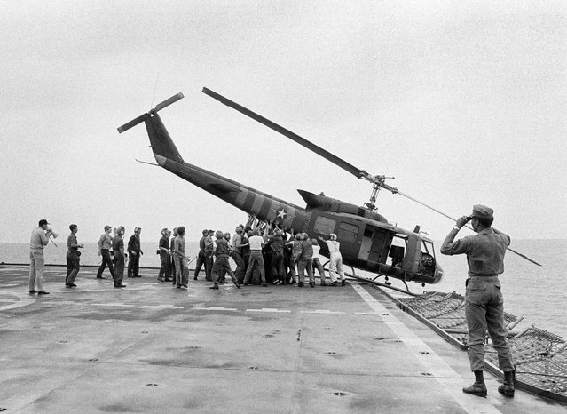 In this Tuesday, April 29, 1975 file photo, U.S. Navy personnel aboard the USS Blue Ridge push a helicopter into the sea off the coast of Vietnam in order to make room for more evacuation flights from Saigon. The helicopter had carried Vietnamese people fleeing Saigon as North Vietnamese forces closed in on the capital. (Photo by AP Photo)