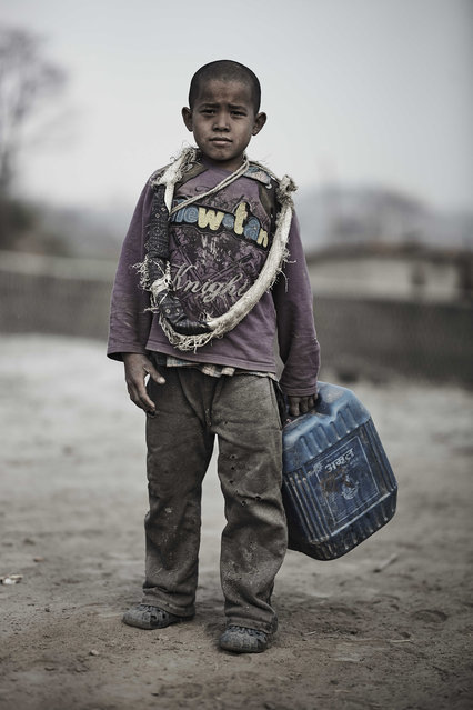 A young kiln worker carries a tub of water home in Kathmandu Valley, Nepal, 22 February 2015. (Photo by Jan Moeller Hansen/Barcroft Images)