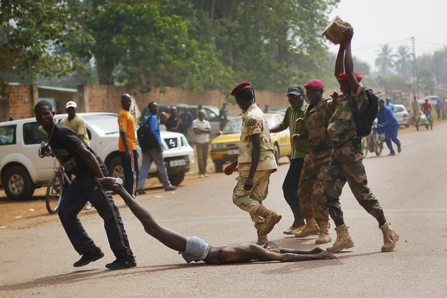 Newly enlisted FACA (Central African Armed Forces) soldiers drag the lifeless body of a suspected Muslim Seleka militiaman moments after Central African Republic Interim President Catherine Samba-Panza addressed the troops in Bangui, Wednesday February 5, 2014. The victim was lynched by hundreds of recruits, pelting him with bricks and mutilating his body with knives. (Photo by Jerome Delay/AP Photo)