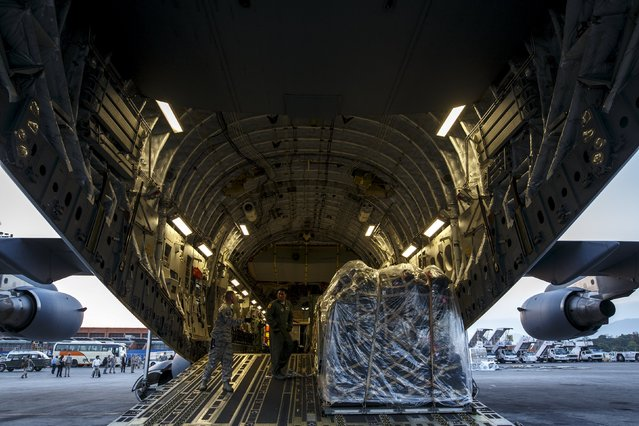 U.S. Air Force (USAF) personnel prepare to unload equipment from a C-17A Globemaster III aircarft after it landed at Tribhuvan International in Kathmandu, Nepal, May 5, 2015. (Photo by Athit Perawongmetha/Reuters)
