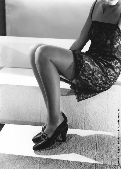 A black lace slip worn with stockings and buckled shoes, 1936