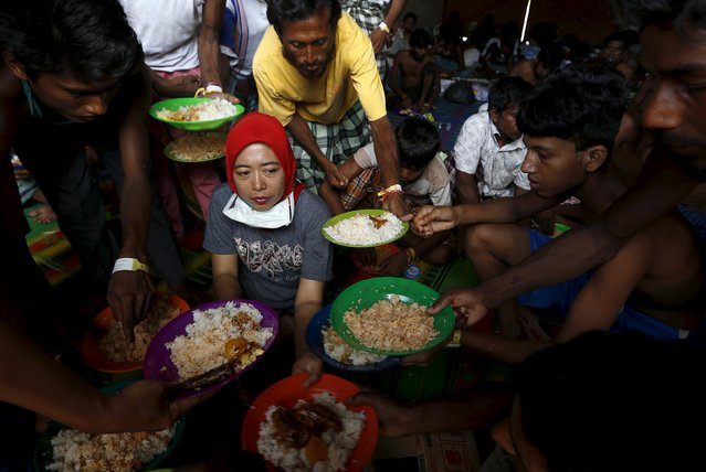 Bangladeshi migrants, who recently arrived in Indonesia by boat, raise up their plates to ask for more food, as breakfast is served by An Indonesian volunter at a shelter in Kuala Langsa, in Indonesia's Aceh Province, May 19, 2015. (Photo by Reuters/Beawiharta)