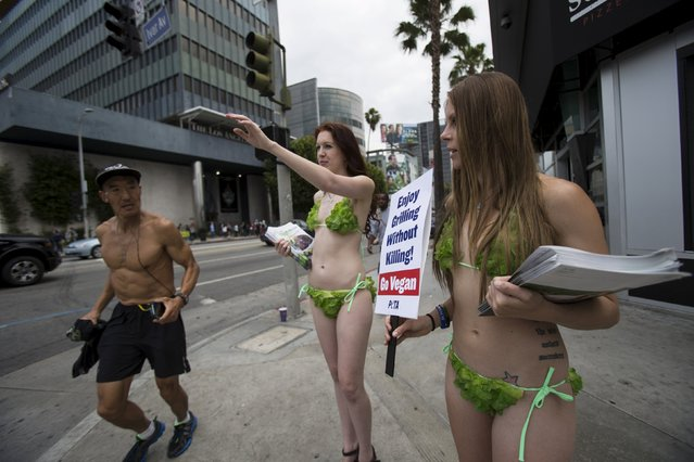 Activists from People for the Ethical Treatment of Animals (PETA) hold signs promoting a vegan diet as a man jogs past in Los Angeles, California May 21, 2015. (Photo by Mario Anzuoni/Reuters)