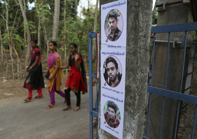 """Indian girls walk past posters displaying photographs of three friends, from top, Vishnu, Athiraj and Brijesh who died after a massive fire broke out Sunday during a fireworks display at the Puttingal temple complex in Paravoor village, Kollam district, southern Kerala state, India, April 11, 2016. Medical teams on Monday tended to hundreds of people injured in a massive fire that killed more than a hundred, while authorities searched for those responsible for illegally putting on the fireworks display that caused the weekend blaze. The posters in Malayalam read, """"Homage"""". (Photo by Aijaz Rahi/AP Photo)"""