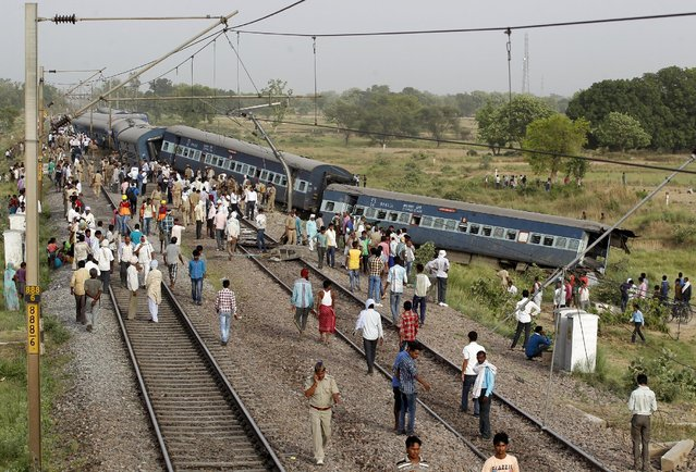 Police and onlookers gather near the damaged coaches of a passenger train after it derailed in Kaushambi district, in the northern state of Uttar Pradesh, India, May 25, 2015. At least two passengers were killed and seven others injured when eight bogies of a passenger train derailed in the district on Monday, a railway official said. (Photo by Jitendra Prakash/Reuters)