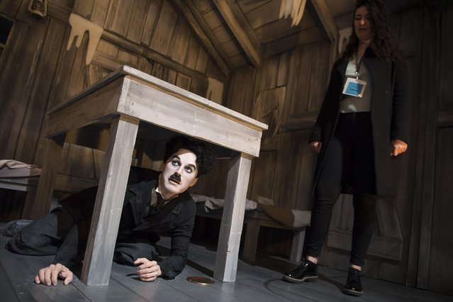 """A visitor looks at a wax figure of actor , filmmaker and composer,  Charlie Chaplin,  during the inauguration and the opening of the museum """"Chaplin's World by Grevin"""" at the Manoir de Ban, in Corsier-Sur- Vevey, Switzerland, Saturday, April 16, 2016. Chaplin, who died in 1977, spent his last 25 years on the 14 hectares (35 acres) estate along the """"Swiss Riviera"""",  at Lake Geneva.   (Photo by Laurent Gillieron/Keystone via AP Photo)"""