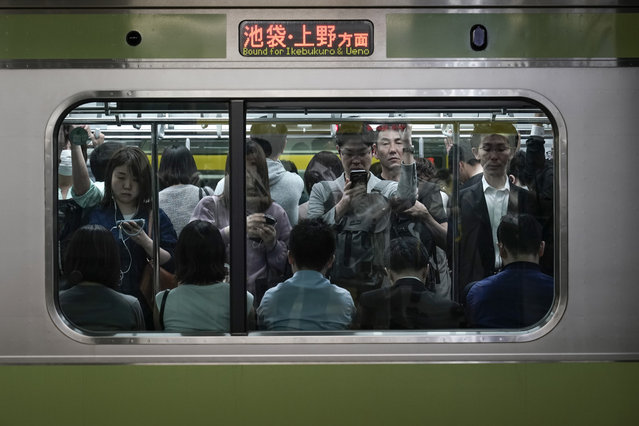 In this Saturday, May 25, 2019, photo, commuters stand in a packed Yamanote Line train while waiting for the train to depart at Shinjuku Station in Tokyo. Want to take a glimpse of daily life in downtown Tokyo? Take a ride on the Yamanote loop line. For most Tokyoites, the line means an incredibly punctual and efficient transportation system for commuting. For tourists, it offers a glimpse into the life of ordinary people living in the city. (Photo by Jae C. Hong/AP Photo)