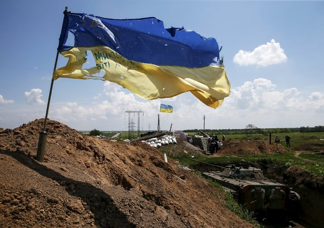 """A tattered Ukrainian national flag flutters in the wind at a position held by the Ukrainian armed forces near the town of Maryinka, eastern Ukraine, June 5, 2015. Ukraine's president told his military on Thursday to prepare for a possible """"full-scale invasion"""" by Russia all along their joint border, a day after the worst fighting with Russian-backed separatists in months.  REUTERS/Gleb Garanich"""