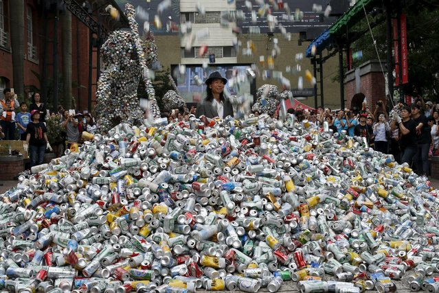 """Artist Chin Chih Yang performs """"Kill Me or Change"""" with 30,000 cans falling and burying the artist underneath a mountain of garbage, at the Museum of Contemporary Art in Taipei, Taiwan April 23, 2016. (Photo by Tyrone Siu/Reuters)"""