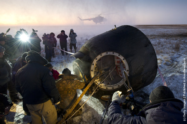 Russian support personnel work to help get Expedition 29 crew members out of the Soyuz TMA-02M spacecraft shortly after the capsule landed