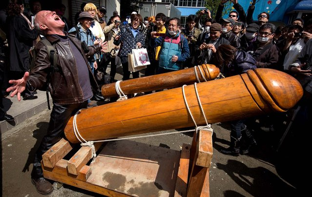 A man poses for photographers with a large wooden phallic sculpture during Kanamara Matsuri (Festival of the Steel Phallus) in Kawasaki, Japan, on April 6, 2014. The festival has become a popular tourist attraction and is used to raise money for HIV awareness and research.  (Photo by Chris McGrath/Getty Images)