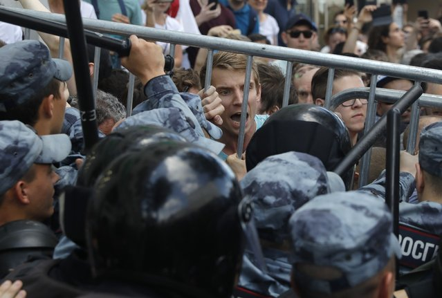 Protesters clash with police during an unsanctioned rally in the center of Moscow, Russia, Saturday, July 27, 2019. (Photo by Pavel Golovkin/AP Photo)