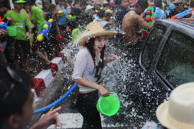 Tourists and Thai residents take part in a city-wide water fight during the Songkran water festival on April 14, 2014 in Chiang Mai, Thailand. The Songkran festival, marking the traditional Thai New Year, is celebrated each year from April 13 to 15. The throwing of water was traditionally a sign of respect and well wishing during the festival. (Photo by Taylor Weidman/Getty Images)
