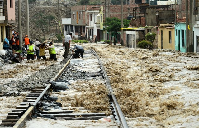 Sections of the central railroad track that follows the Rimac River suffered severe damage by rising water and flash foods in the town of Chosica, at the foot of the Andes mountains east of Lima, on March 18, 2017. (Photo by Cris Bouroncle/AFP Photo)
