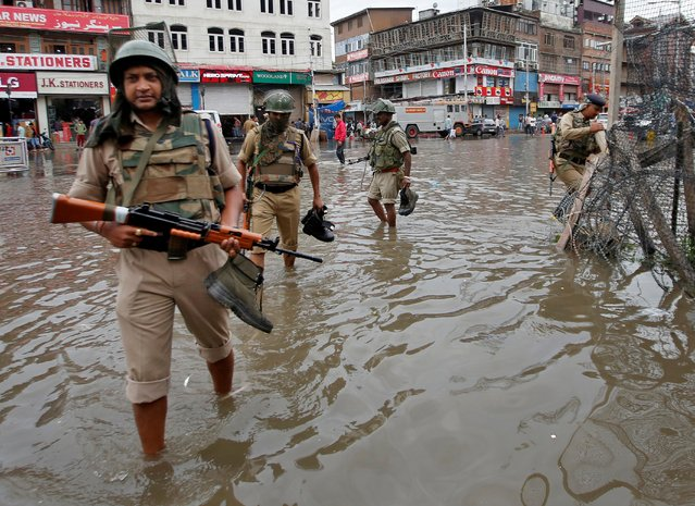 India's Central Reserve Police Force (CRPF) personnel carry their shoes as they wade through a water-logged street after heavy rain in Srinagar August 1, 2019. (Photo by Danish Ismail/Reuters)