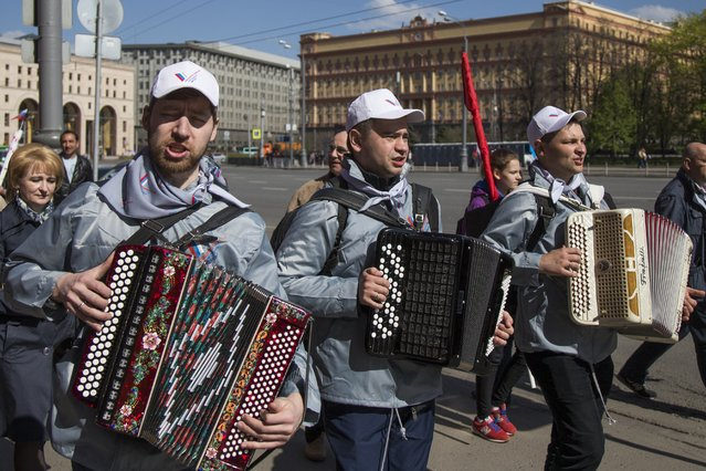 Russians play accordions as they walk near the building of the Federal Security Service (FSB, Soviet KGB successor) in Lubyanskaya Square to mark May Day in Moscow, Russia, Sunday, May 1, 2016. As in Soviet times, about one hundred thousand of cheerful workers paraded across Red Square despite a chilly rain, but instead of red flags with the Communist hammer and sickle, they waved the blue flags of the dominant Kremlin party and the Russian tricolor. (Photo by Alexander Zemlianichenko/AP Photo)