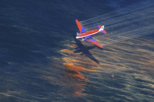 The crew of a Basler BT-67 fixed wing aircraft release oil dispersant over an oil discharge from the mobile offshore drilling unit, Deepwater Horizon, off the shore of Louisiana, in this May 5, 2010 handout photograph. Picture taken, May 5, 2010. BP Plc announced July 2, 2015 it has reached a comprehensive $18.7 billion settlement with the U.S. government and five states. (Photo by Stephen Lehmann/Reuters/U.S. Coast Guard)
