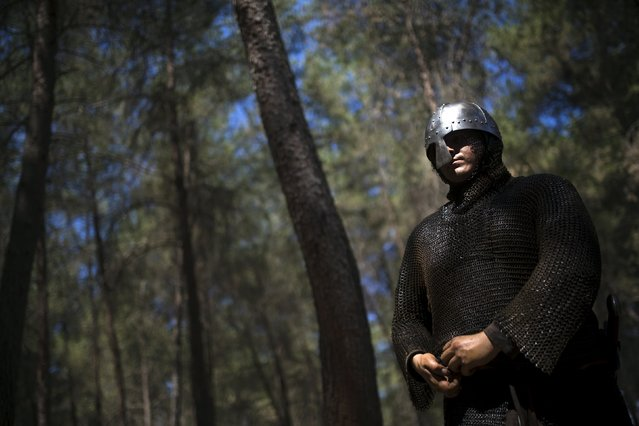 An enthusiast wearing a costume stands in a forest during a re-enactment of a decisive Crusaders battle in northern Israel's Galilee region July 4, 2015. (Photo by Amir Cohen/Reuters)